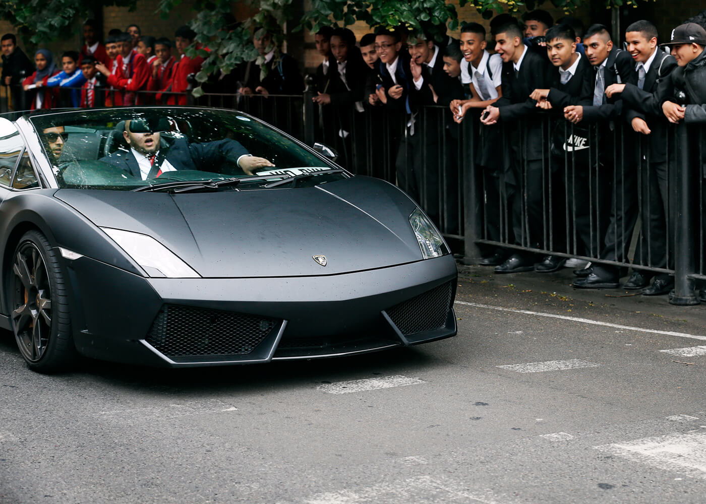 Students watch as Ujjol Hussain, 16, is driven past in a hired Lamborghini during the supercar parade at Swanlea school graduation day.