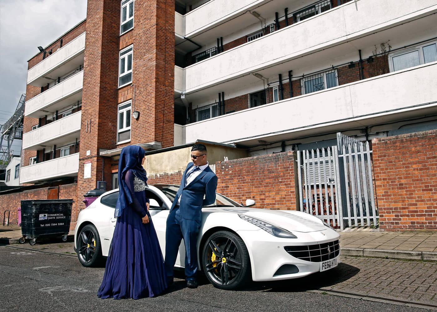Aisha, 16, talks to fellow pupil Tanvir Shahriyar, 16, next to his hired Ferrari, on the Rickman Street estate.