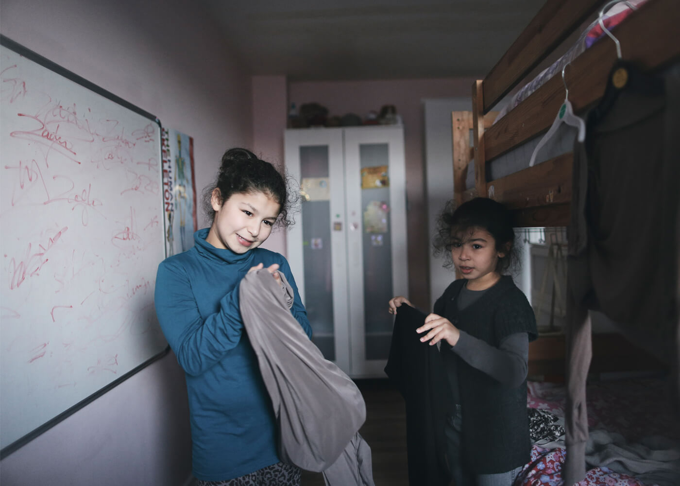 Sanaa and her sister try on clothes in their bedroom.