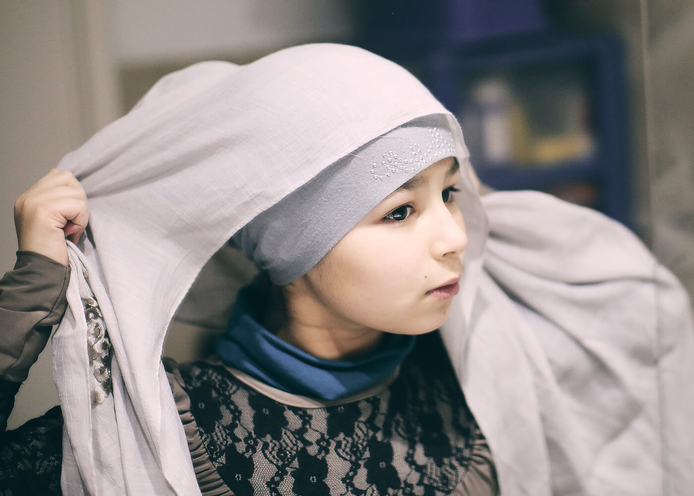 Ten-year-old Sanaa practices putting on her hijab for Islamic Saturday school. She occasionally wears a veil to go to school during the week as well.