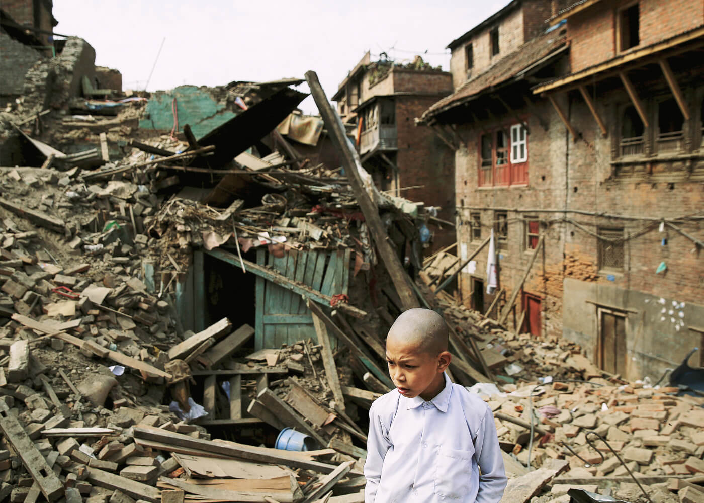 A boy, his head shaved in mourning, searches the rubble of his house for a CD of his favourite music.