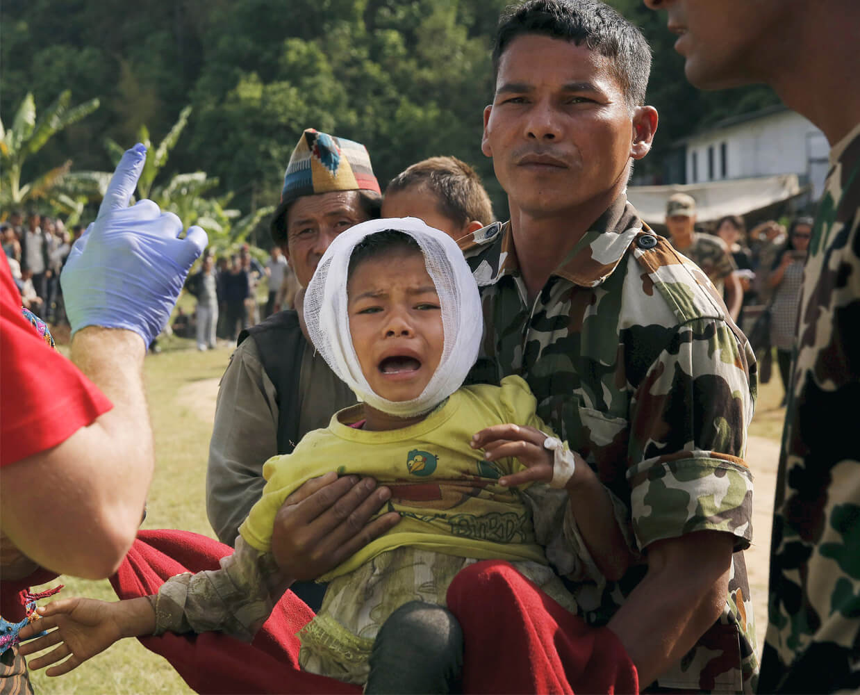 A soldier carries a screaming boy to the hospital tent.