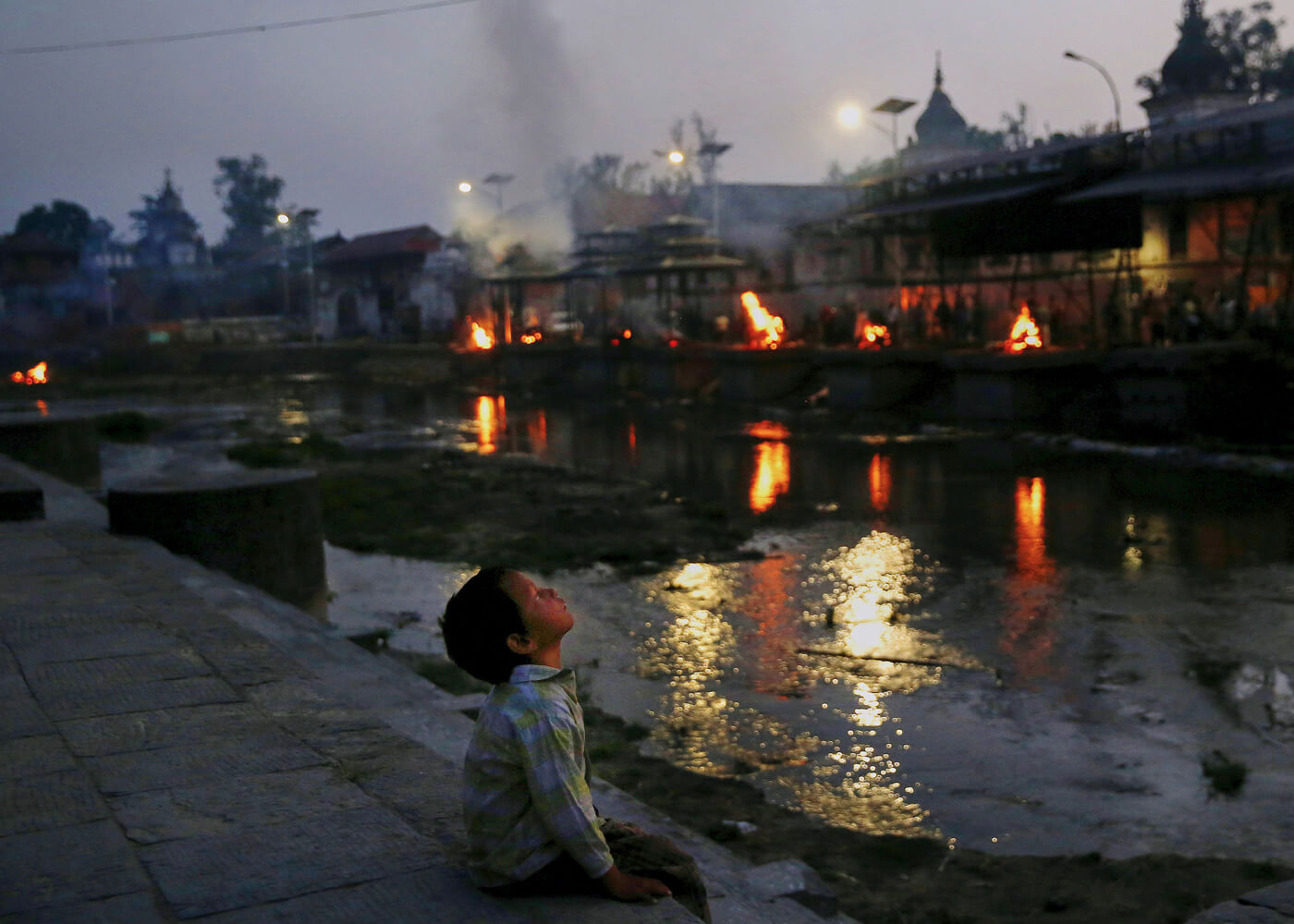 Funeral pyres burn at sunset after more than a week of heavy use following the quake.
