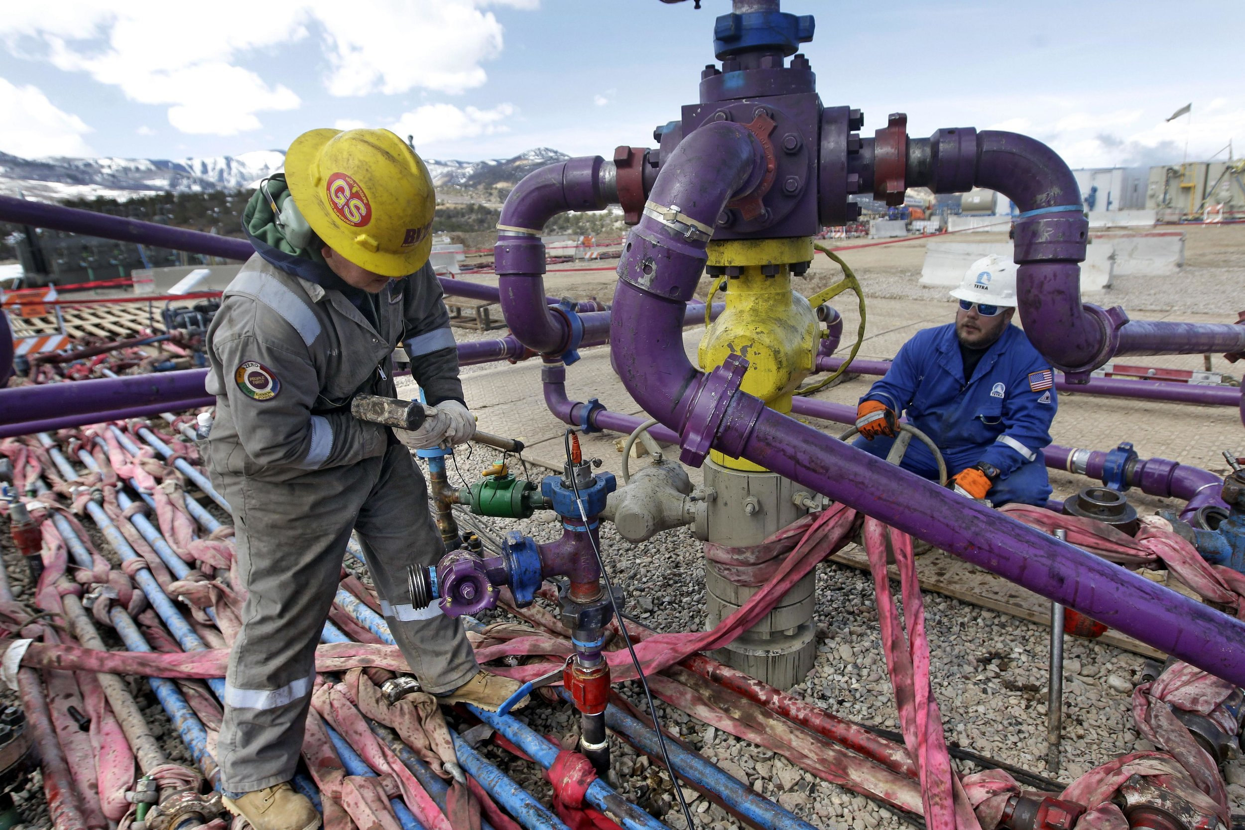 """FILE - In this March 29, 2013 file photo, workers tend to a well head during a hydraulic fracturing operation at an Encana Oil & Gas (USA) Inc. gas well outside Rifle, in western Colorado. The Obama administration is proposing a rule that would require companies that drill for oil and natural gas on federal lands to publicly disclose chemicals used in hydraulic fracturing operations. The new """"fracking"""" rule replaces a draft proposed last year that was withdrawn amid industry complaints that federal regulation could hinder an ongoing boom in natural gas production. (AP Photo/ Brennan Linsley, File)"""