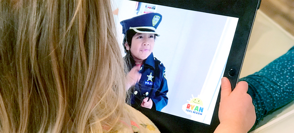 Image of a young girl with an ipad on her lap viewing Ryan of Ryan Toys Review.