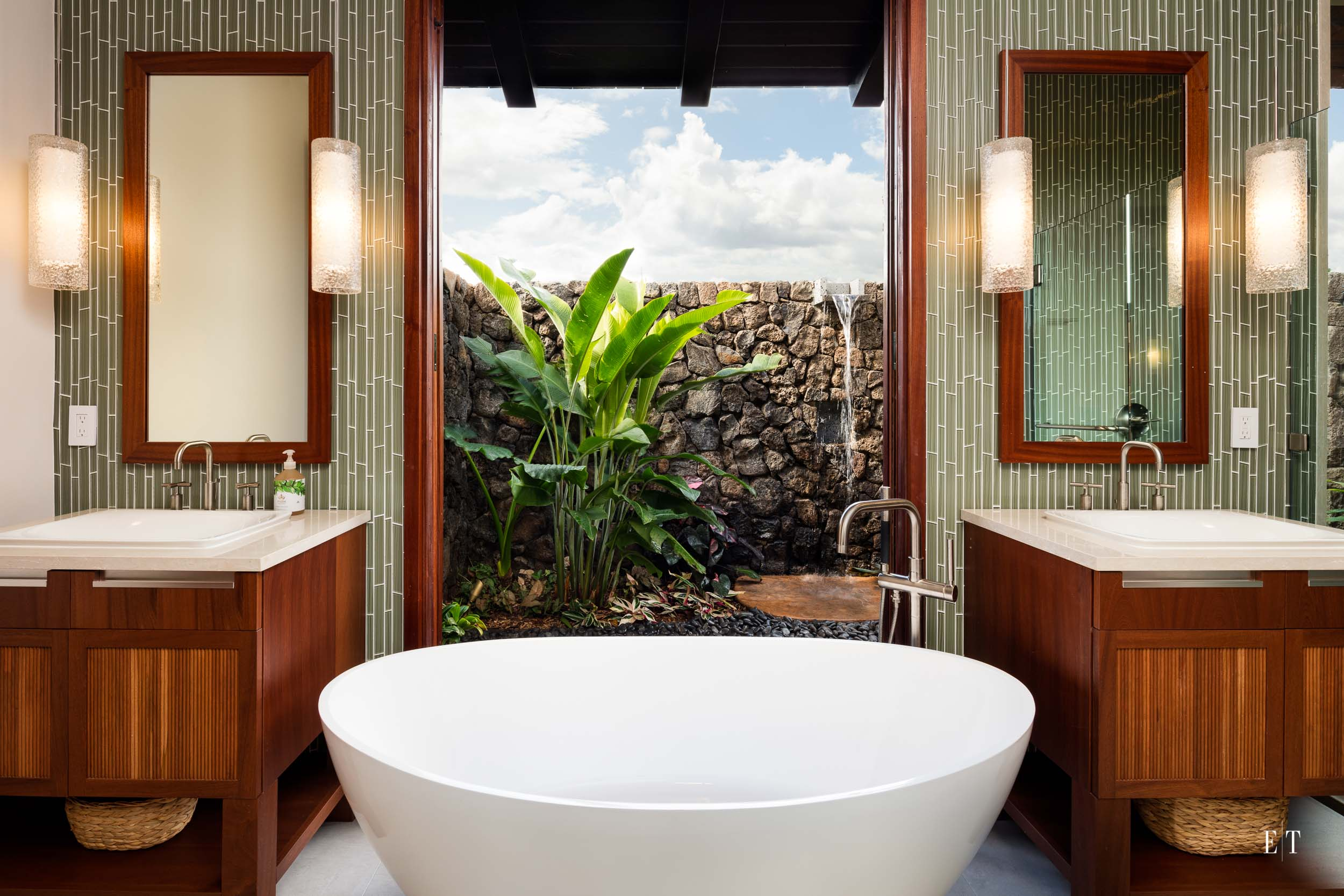 This tub has a view of the outdoor garden and shower