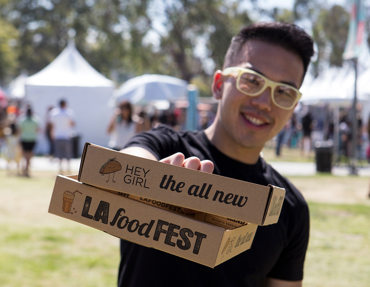 Man showing off our food trays — LA Food Fest | LA's original tasting event | June 29, 2019 at Santa Anita Park, Arcadia, CA