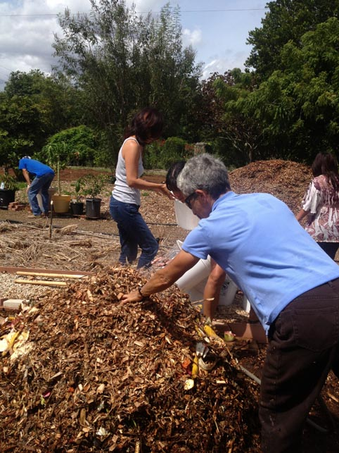 Covering the food waste with another layer of wood chips and water.