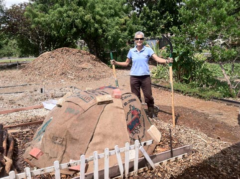 Mindy standing next to her finished hot compost pile that has been fully watered down and covered with burlap bags. (Photo courtesy of Kokua Hawaii Foundation)