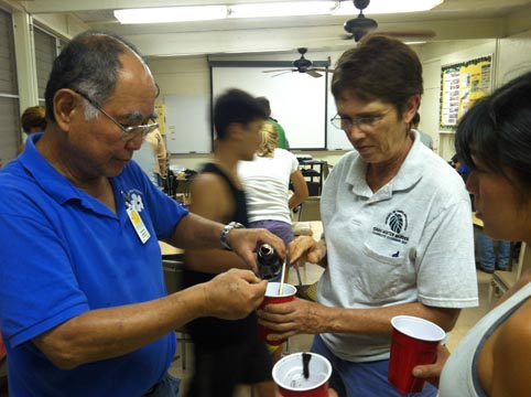 Oahu Master Gardeners & Aina in School docent carefully measuring molasses (food for the EM to grow).