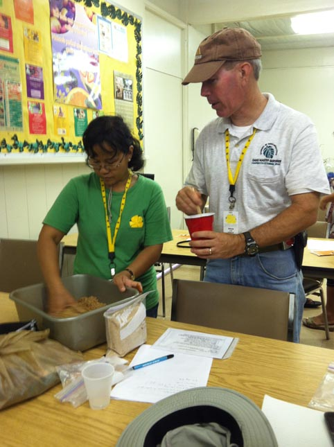 Oahu Master Gardeners following the instructions on making EM Bokashi and checking for right moisture content.