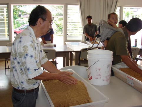 Participants carefully, breaking down the Organic Rice Bran EM® Bokashi made previously.