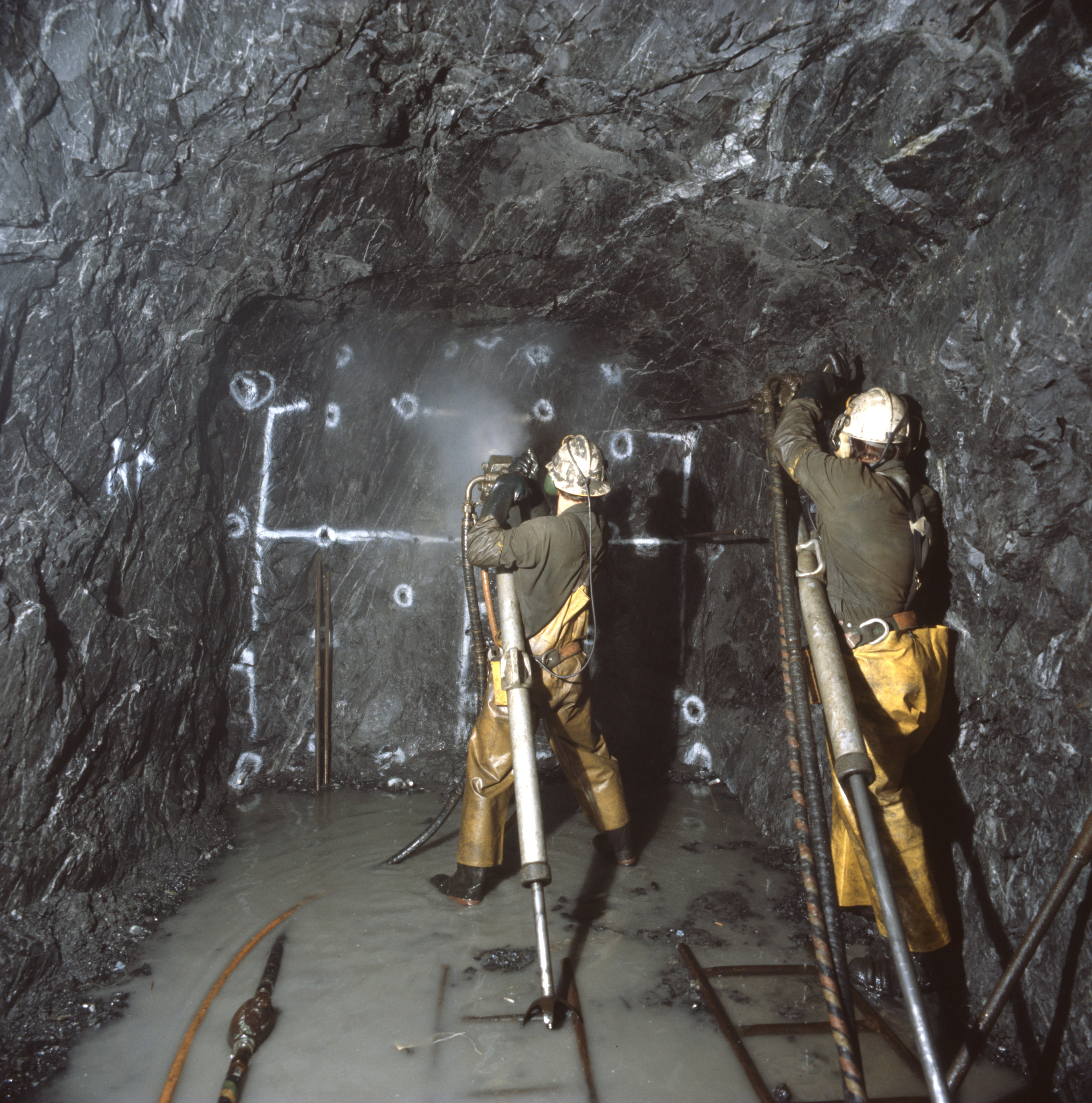 Drillers with jack-leg drills at a face in a small gold mine.