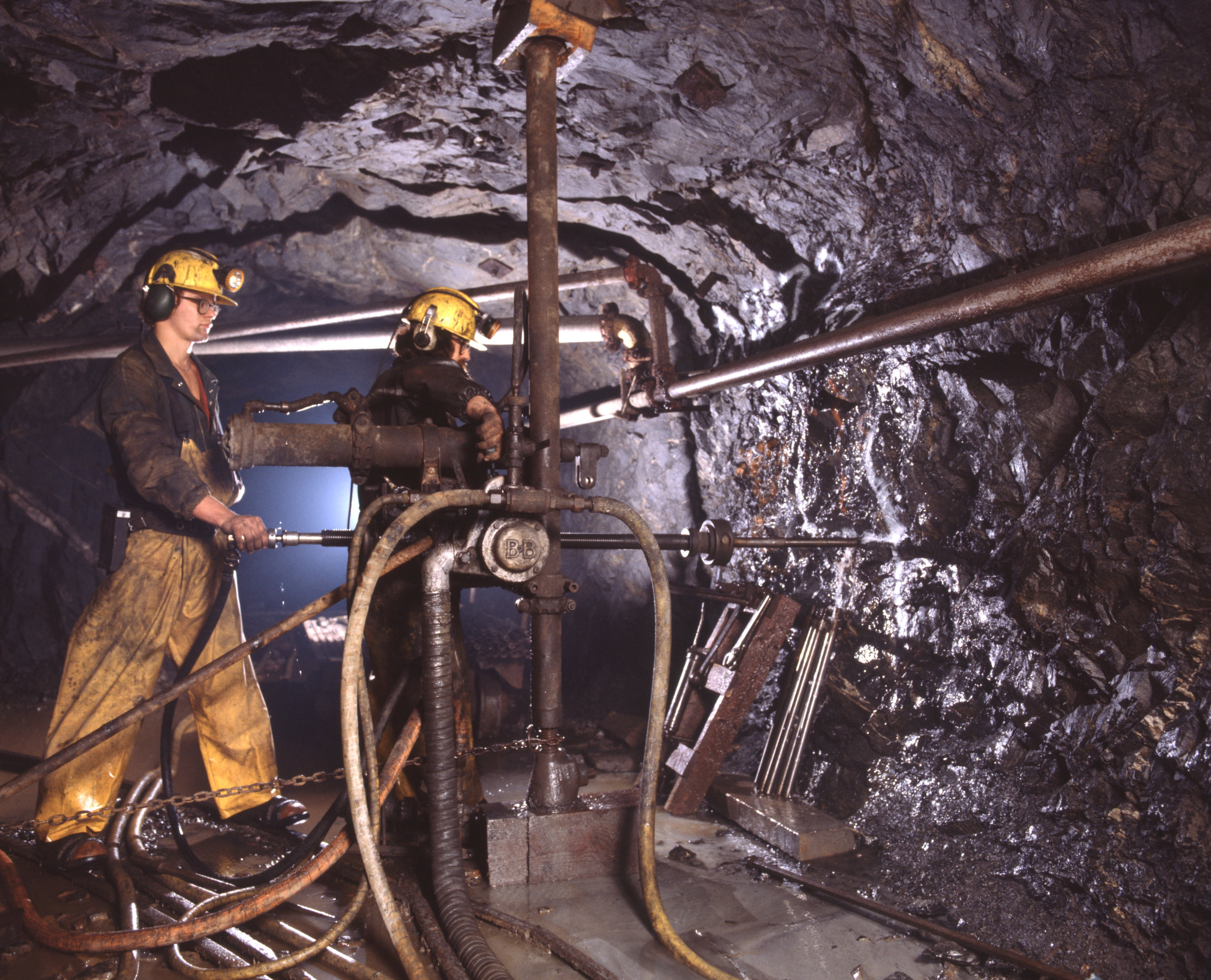 Miners operate diamond drill in drift at Dickenson Mine.