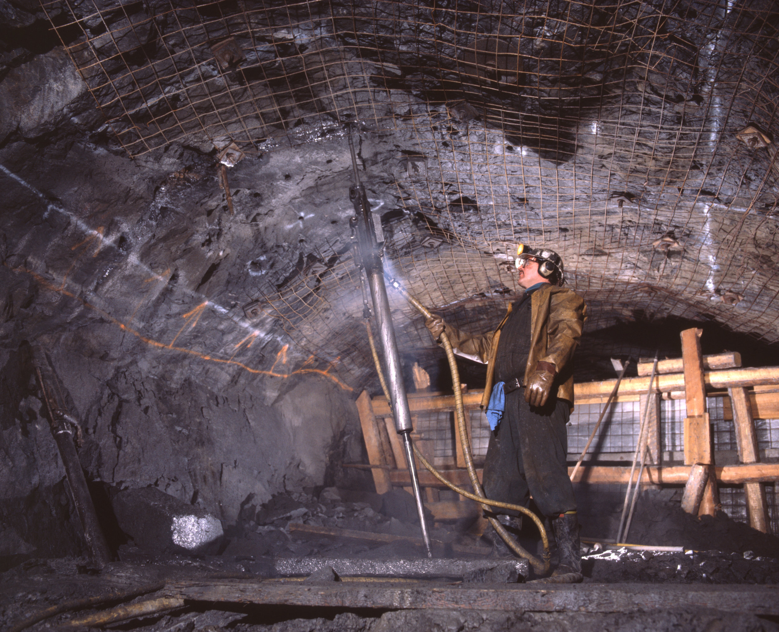 At a small gold mine, miner drills in drift for installation of roofing bolts.