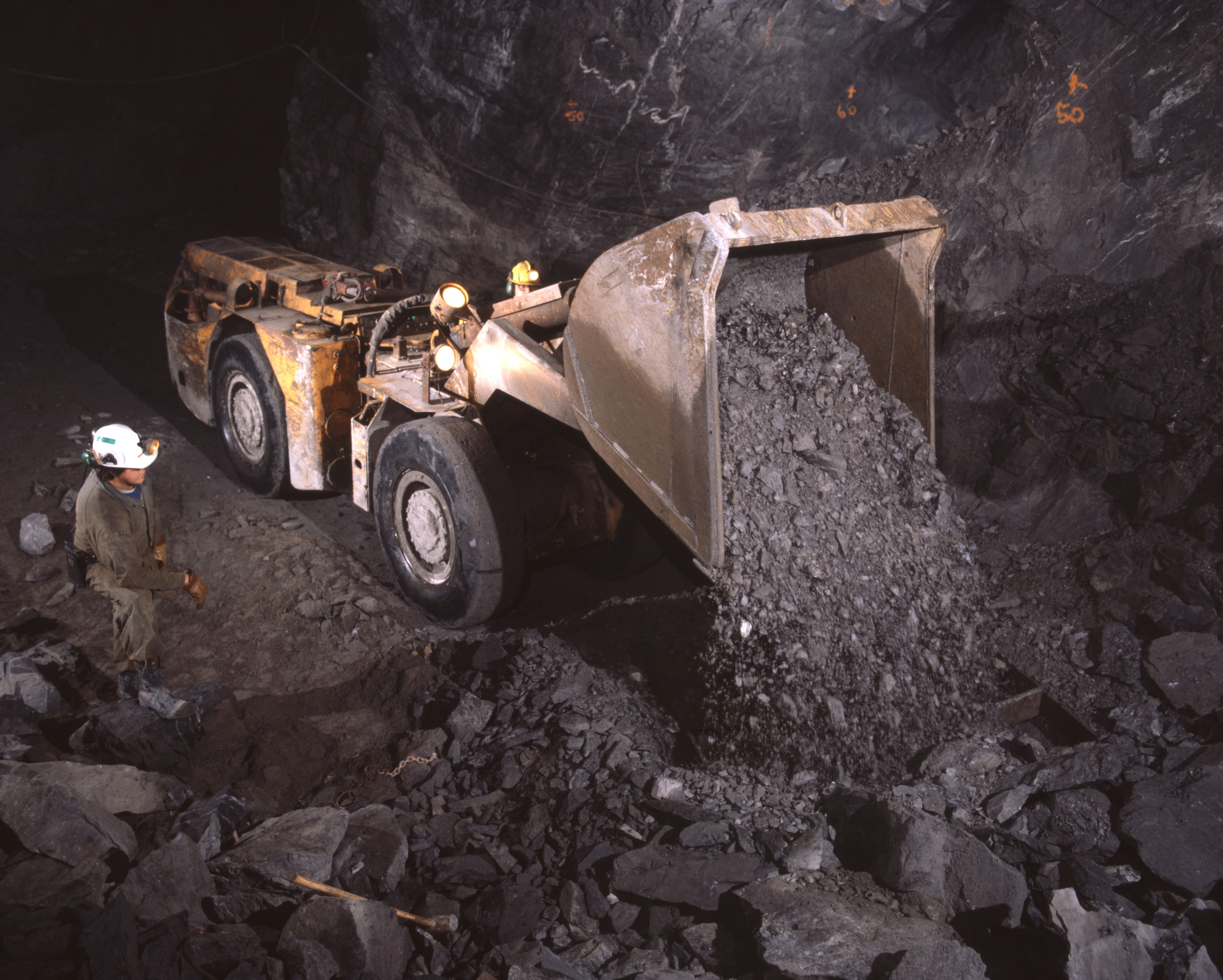 Mucking machine dumps load of ore into grizzly at a small gold mine.