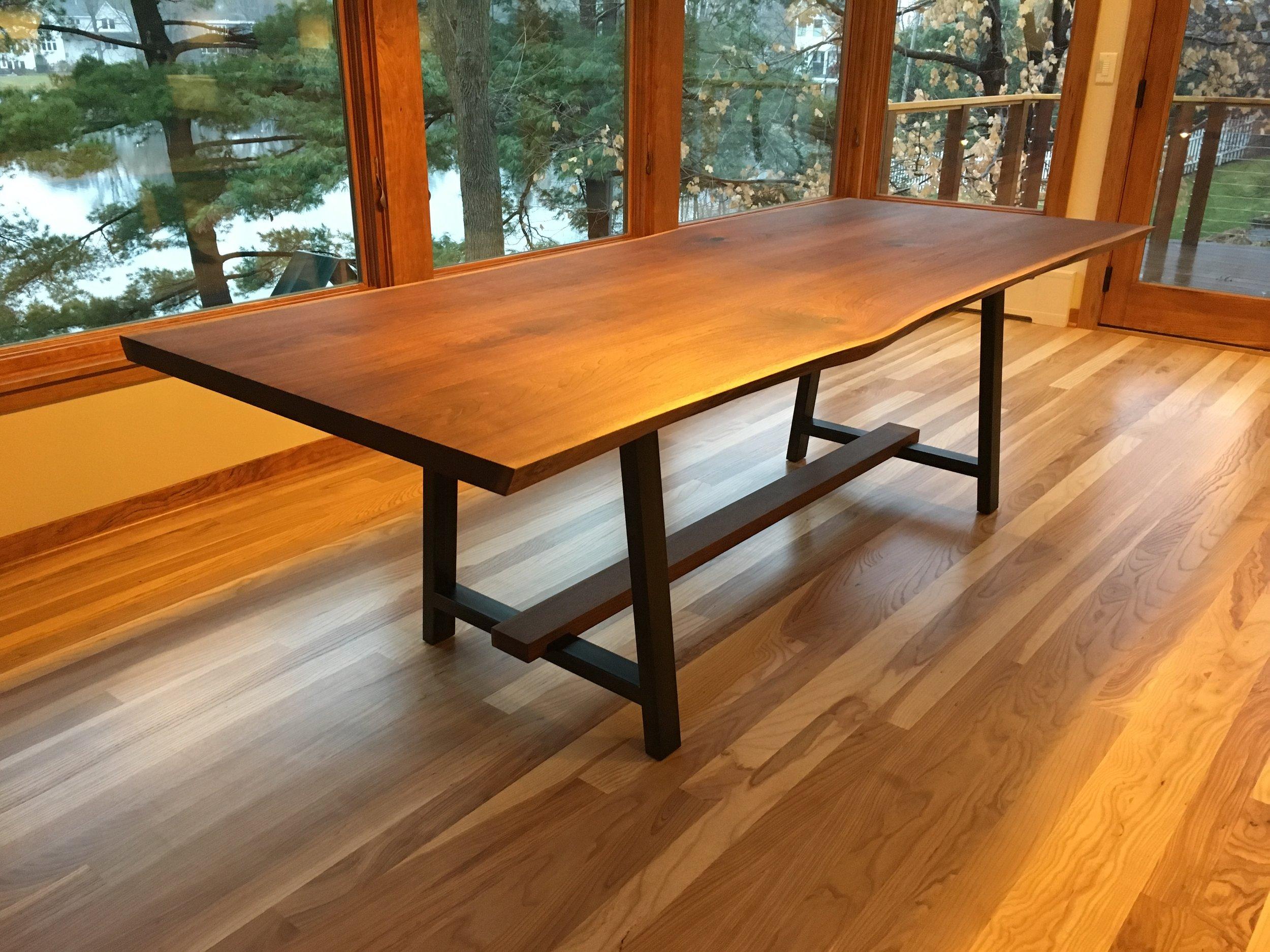 Custom live edge walnut dining table with steel legs.