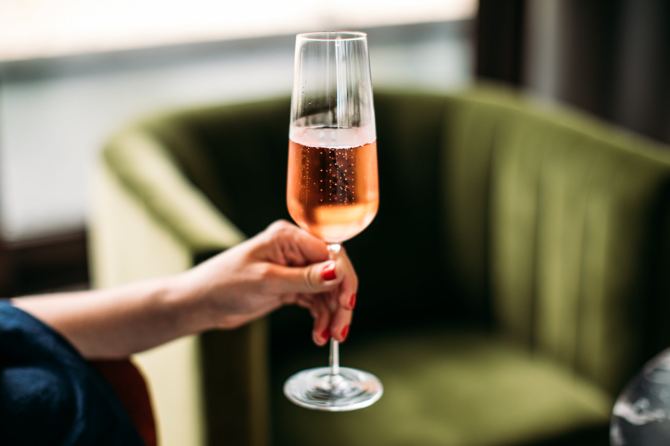 glass holding rose champagne