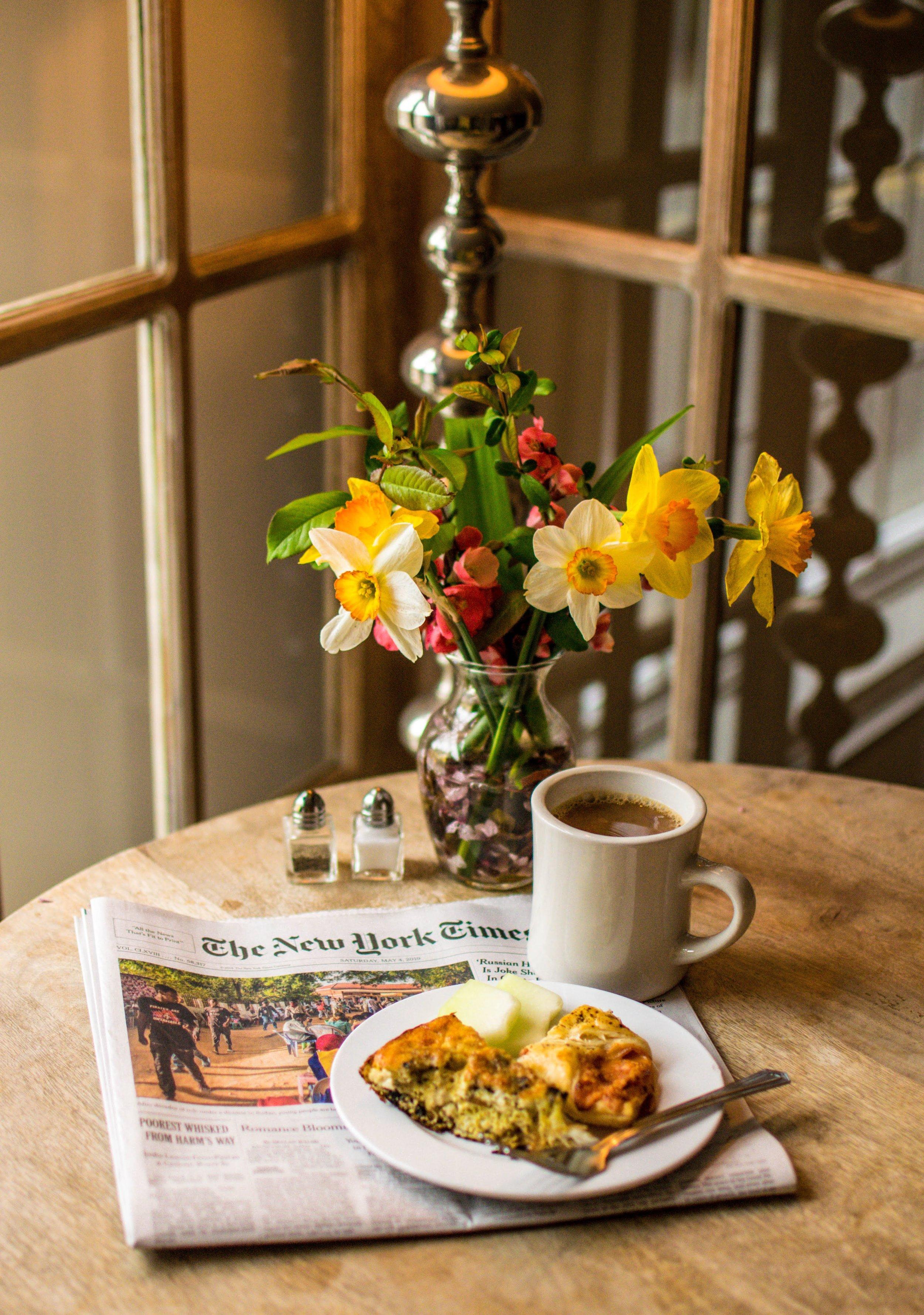 Breakfast table with flowers, coffee, food