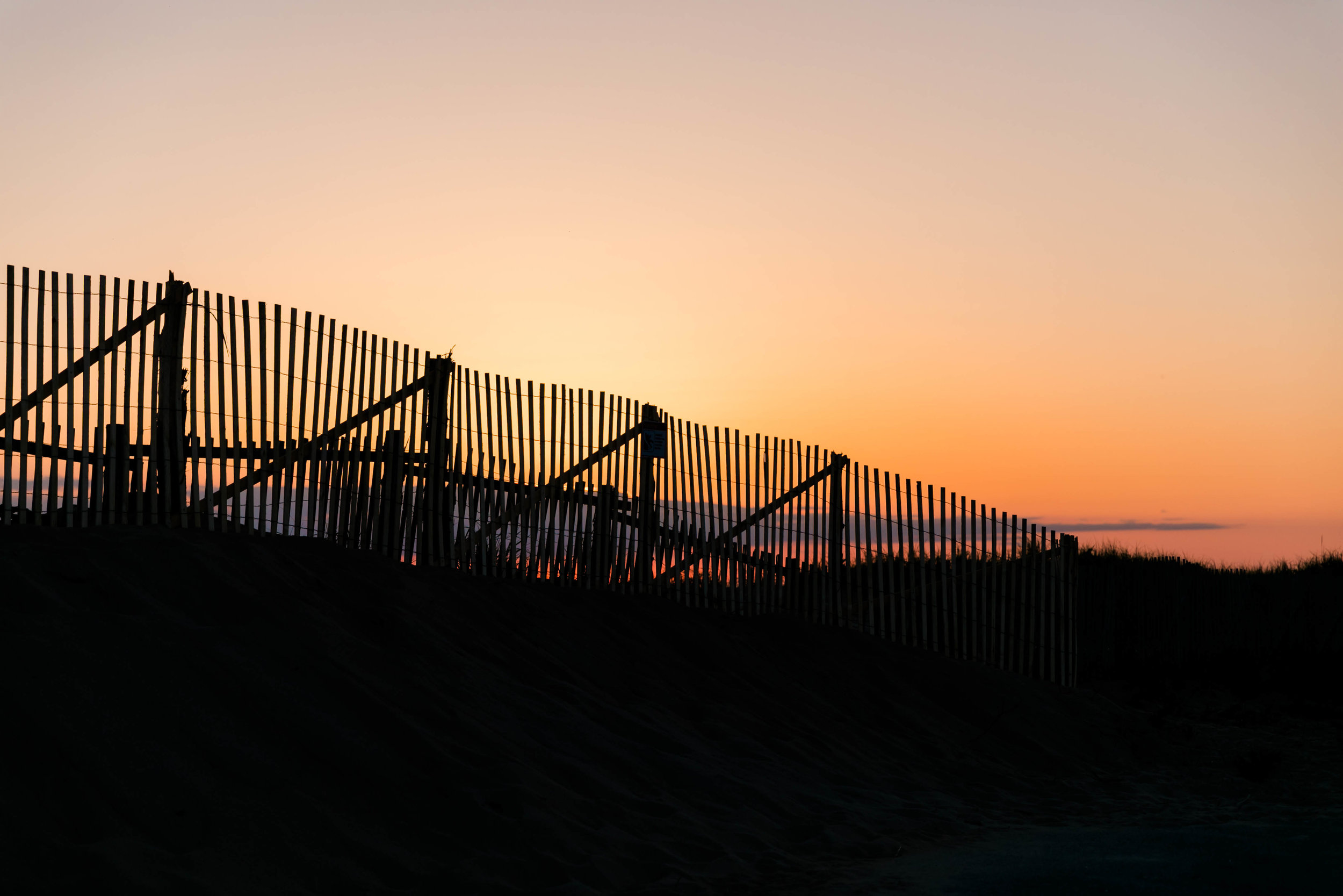 Sun setting over a fence in Provincetown