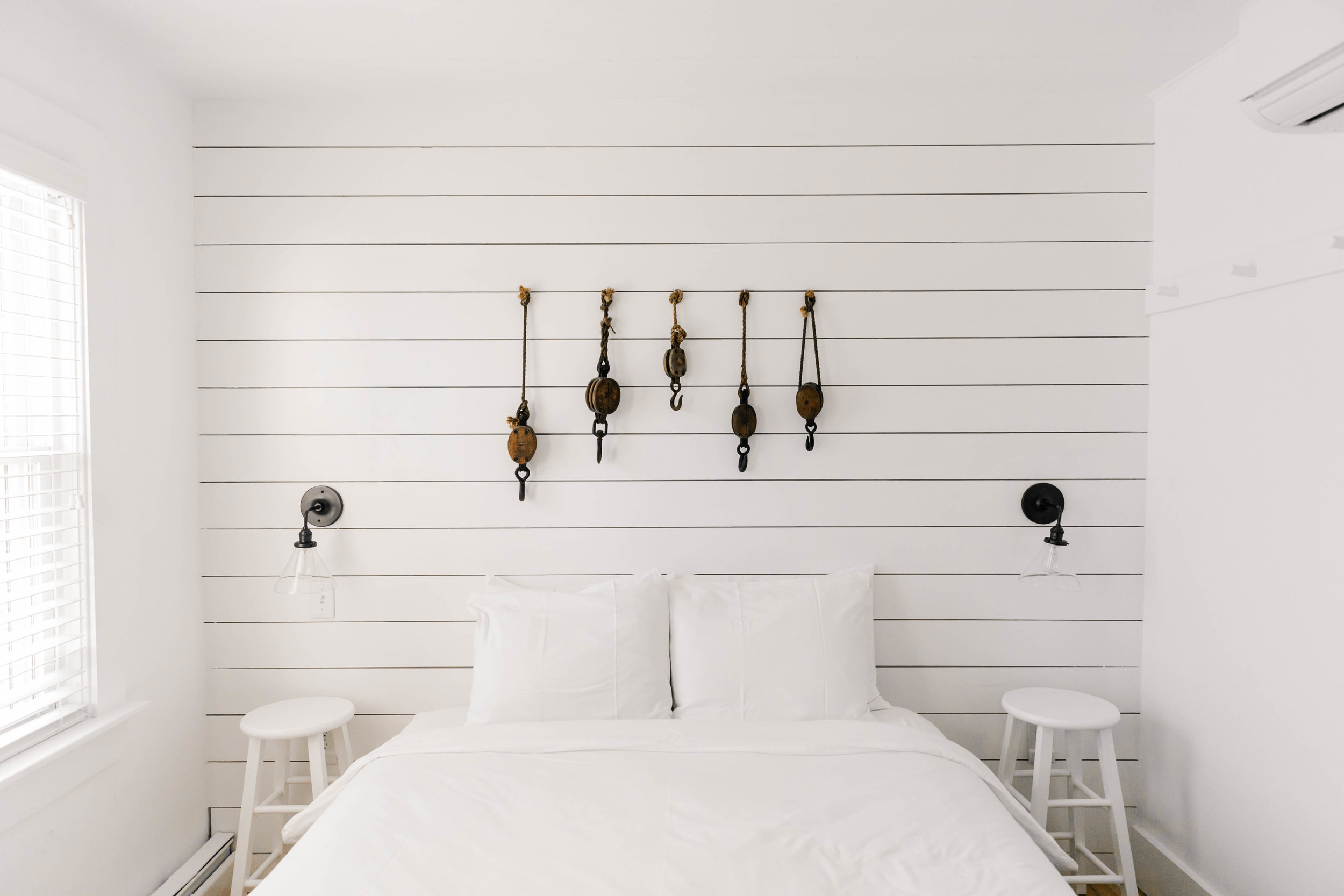 White bed in white room with hanging art objects