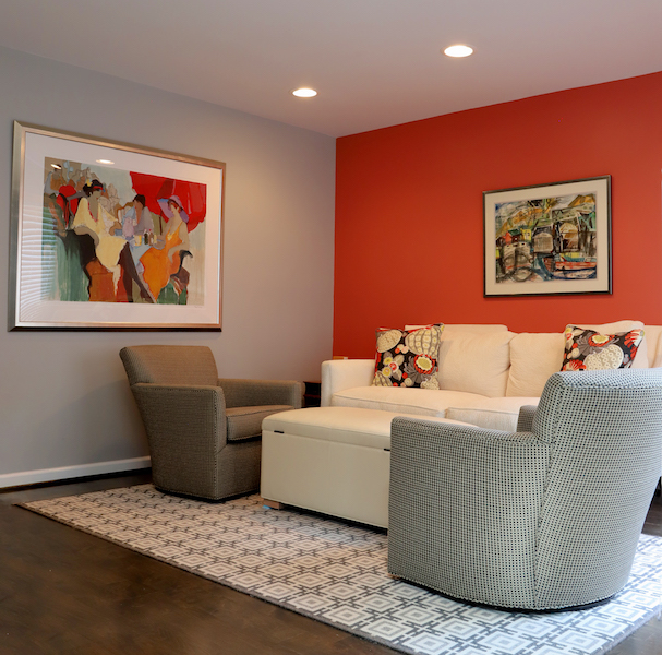 Taking a narrow space and converting it into a cozy conversation-friendly TV viewing area with swivel chairs as well as a storage ottoman that holds throws. A great reading area in bedroom.