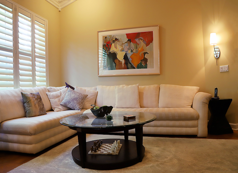 This sofa was purchased for another home. My upholsterer refreshed it for this condo. By adding end tables, a glass-topped cocktail table, a throw rug and lighting. An entirely new and exciting but comfortable mood was created.