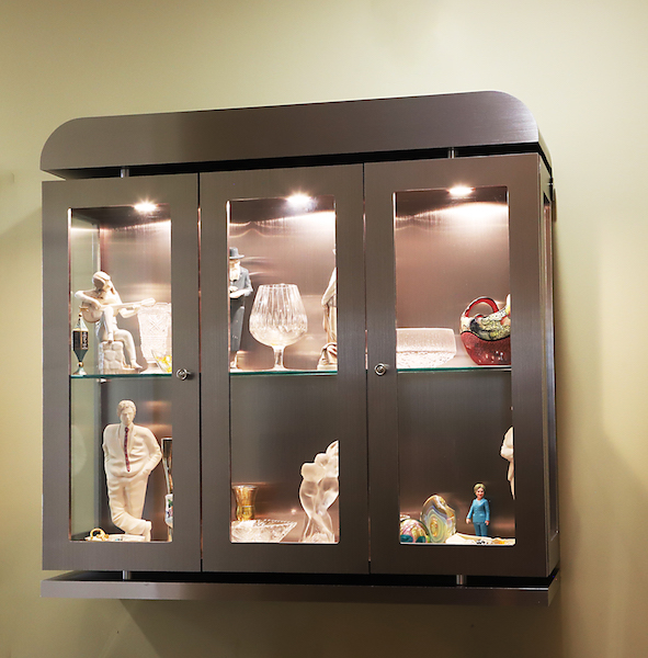 I designed and had my furniture maker create this lighted floating display cabinet in metal with framed glass doors and sides and thick shelves. This can be viewed from all angles. Metal accents were added for EXTRA WOW!
