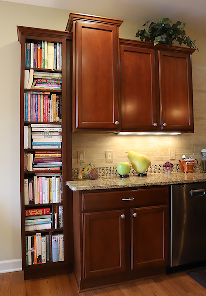 I designed and had my furniture maker add an open bookcase cabinet to an existing kitchen. We matched the color and crown perfectly so that it looked as if it was intended to be there, not as a later add-on.