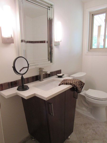 The full remodel of this very narrow bathroom vanity detail that allows the door to close and still allows room on the quartz counter top. The vertical tile back splash is used in the tub as well.