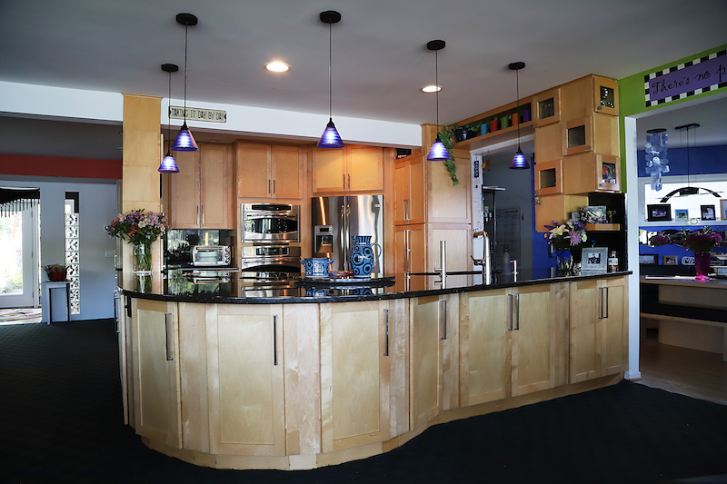 A very large work surface with lots of storage below on both sides. A supporting pole houses spices. The floating cabinets on the right house dinnerware, glasses, and display-even over pass-through. Pendant lights keep it airy!