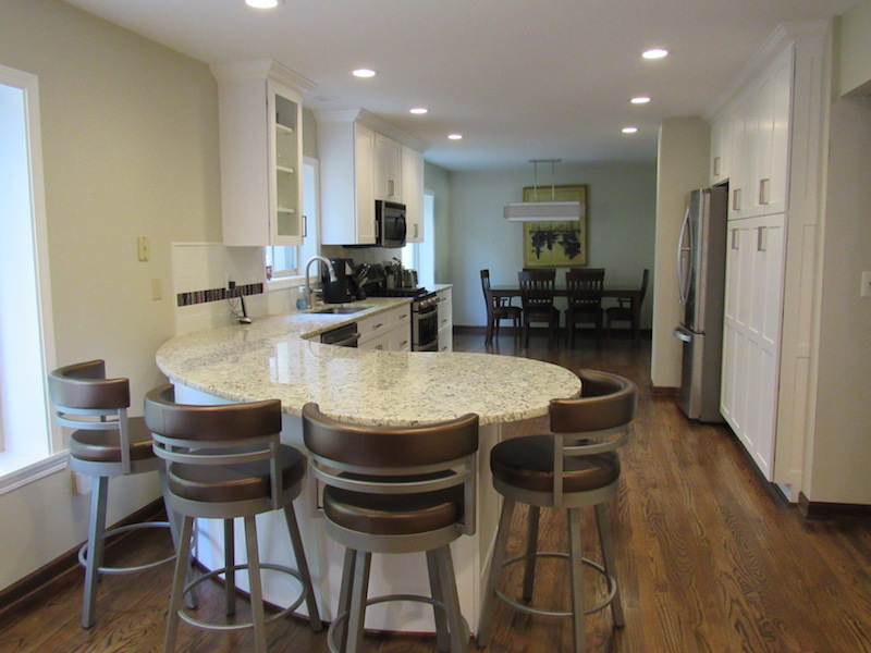 By removing the wall between the kitchen and dining room, I was able to extend the kitchen cabinets to the other window and create an open look. The curved eating island has lots of storage on the other side.