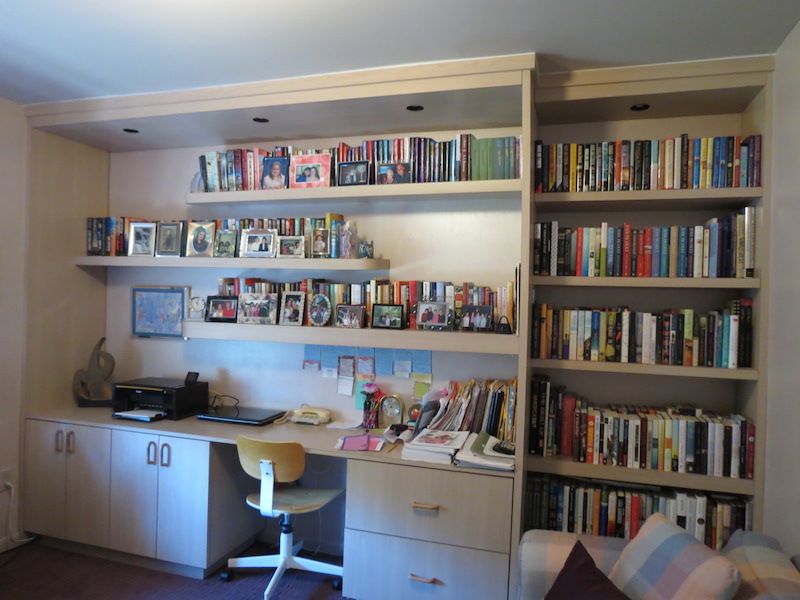 I custom-designed a home office work station with display, lighting, file space, storage, and bookcase to fit the whole wall for maximum usage. The floating shelf above the work area is also lighted.