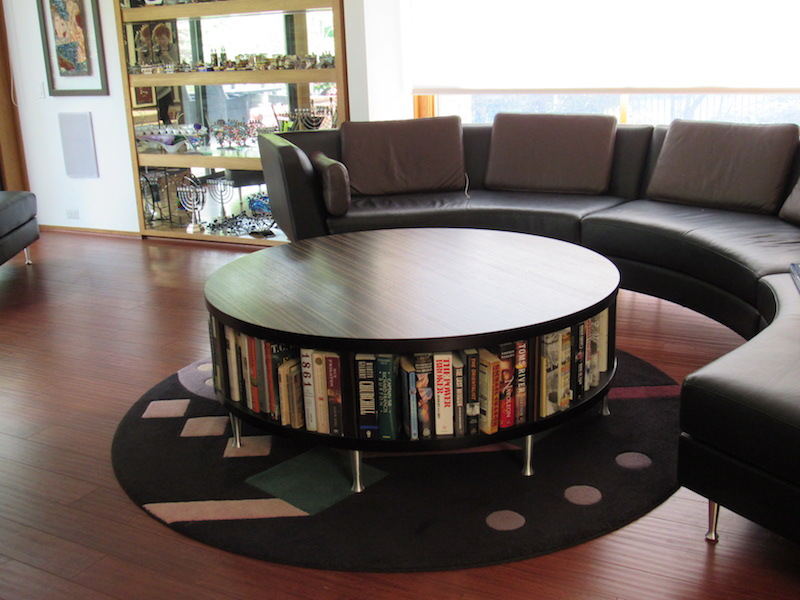 Building a custom table in zebra wood to display books with a storage cabinet on back side for throws as well as matching the sofa legs created a unique look.