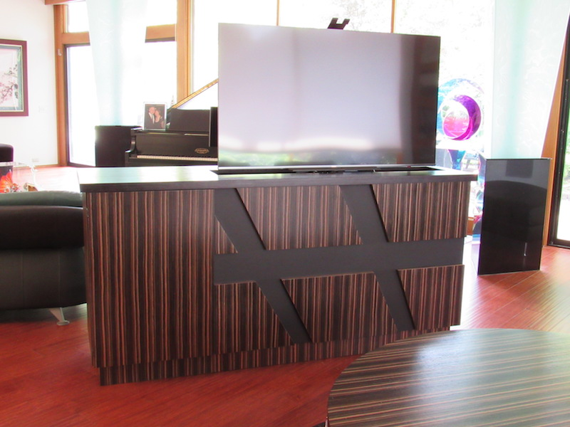 Building a custom TV unit in zebra wood that houses the audio/video and is finished on all four sides divides the seating areas in this room. The TV disappears inside when not in use.