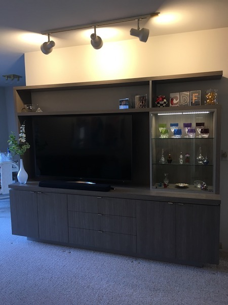 A custom wall unit was designed to hold a big-screen TV, easy closed audio accessibility, storage, open display and glass-enclosed and lighted closed display for a wow factor!
