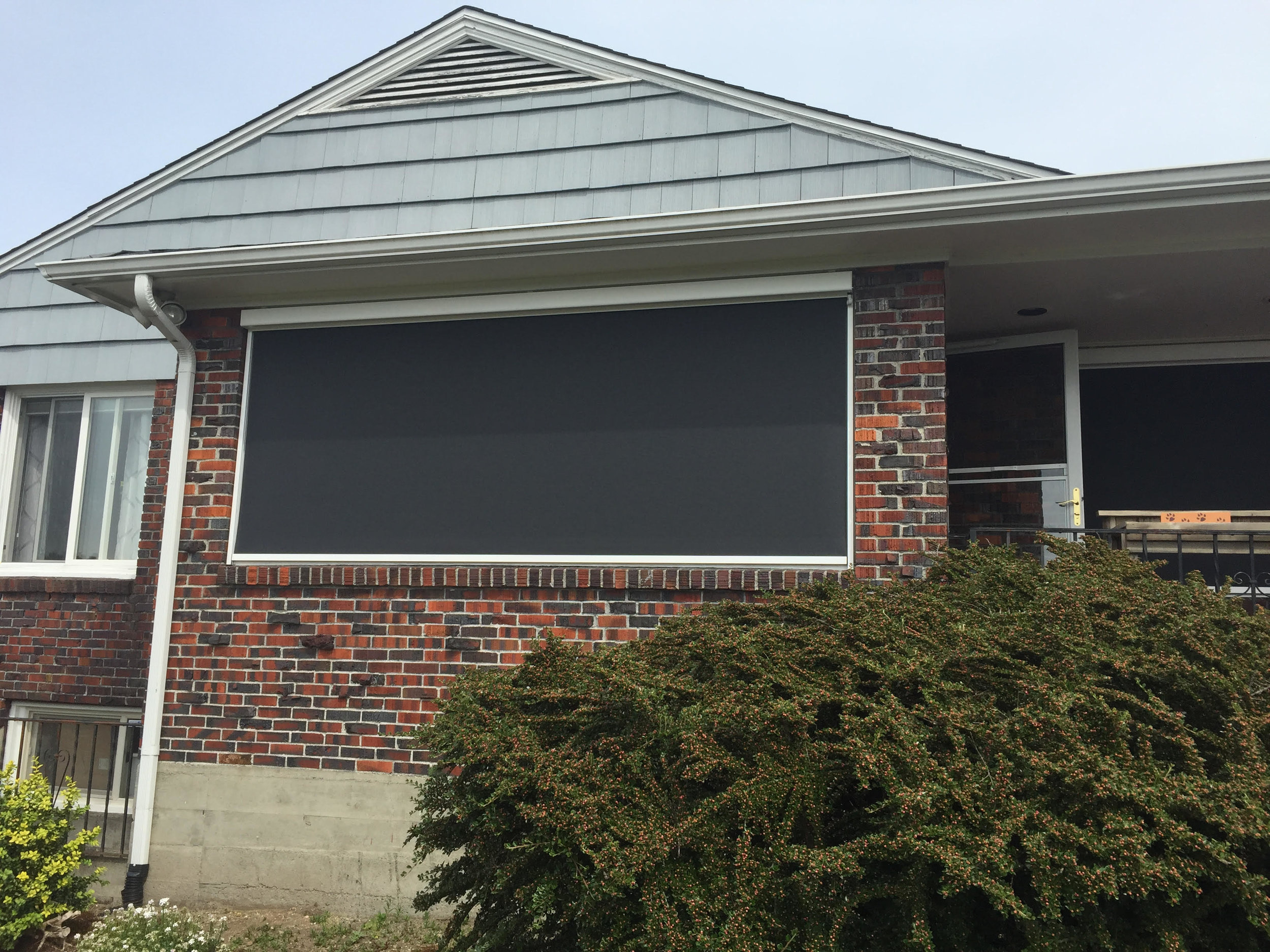 Large Motorized Exterior Shade Enclosed Between Brick Surround