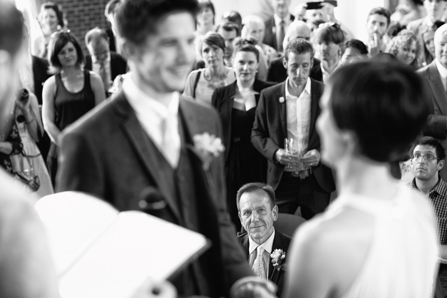 Reportage wedding photography of proud father watching bride make marriage vows