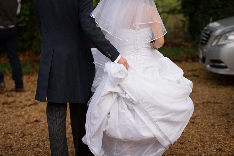 Lains Barn wedding groom carrying bride's train