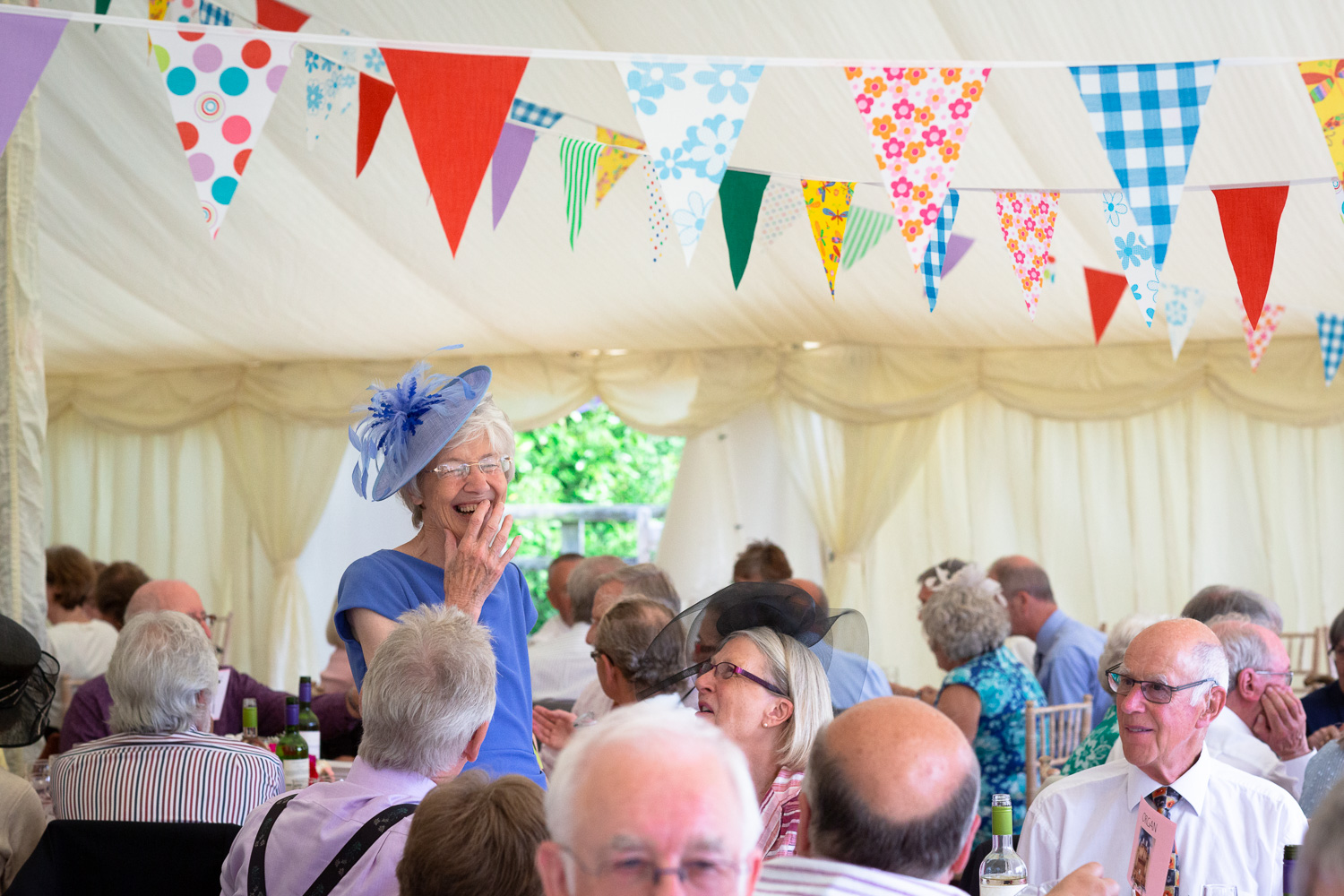 Guest laughter in marquee with bunting at wedding celebration