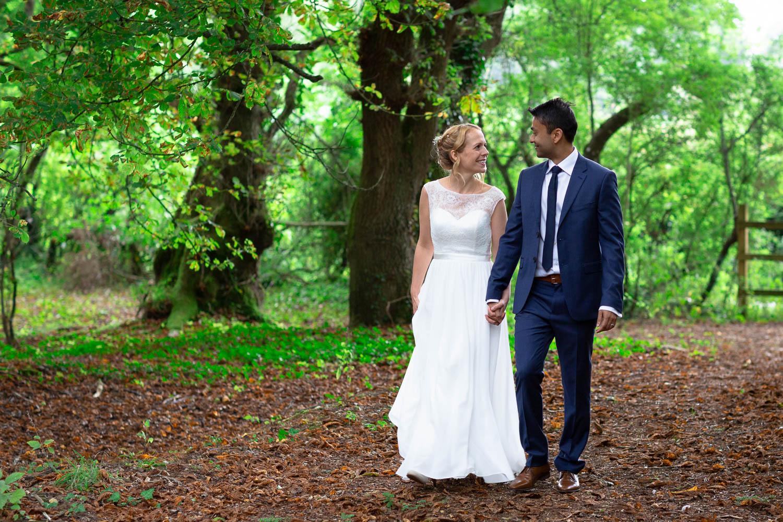 Bride and groom strolling in woods