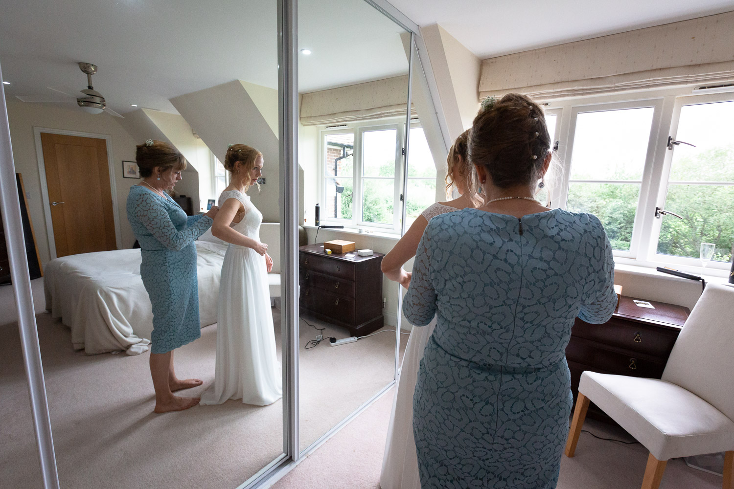 Wedding photography portfolio bride's mother helps with dress during bridal prep