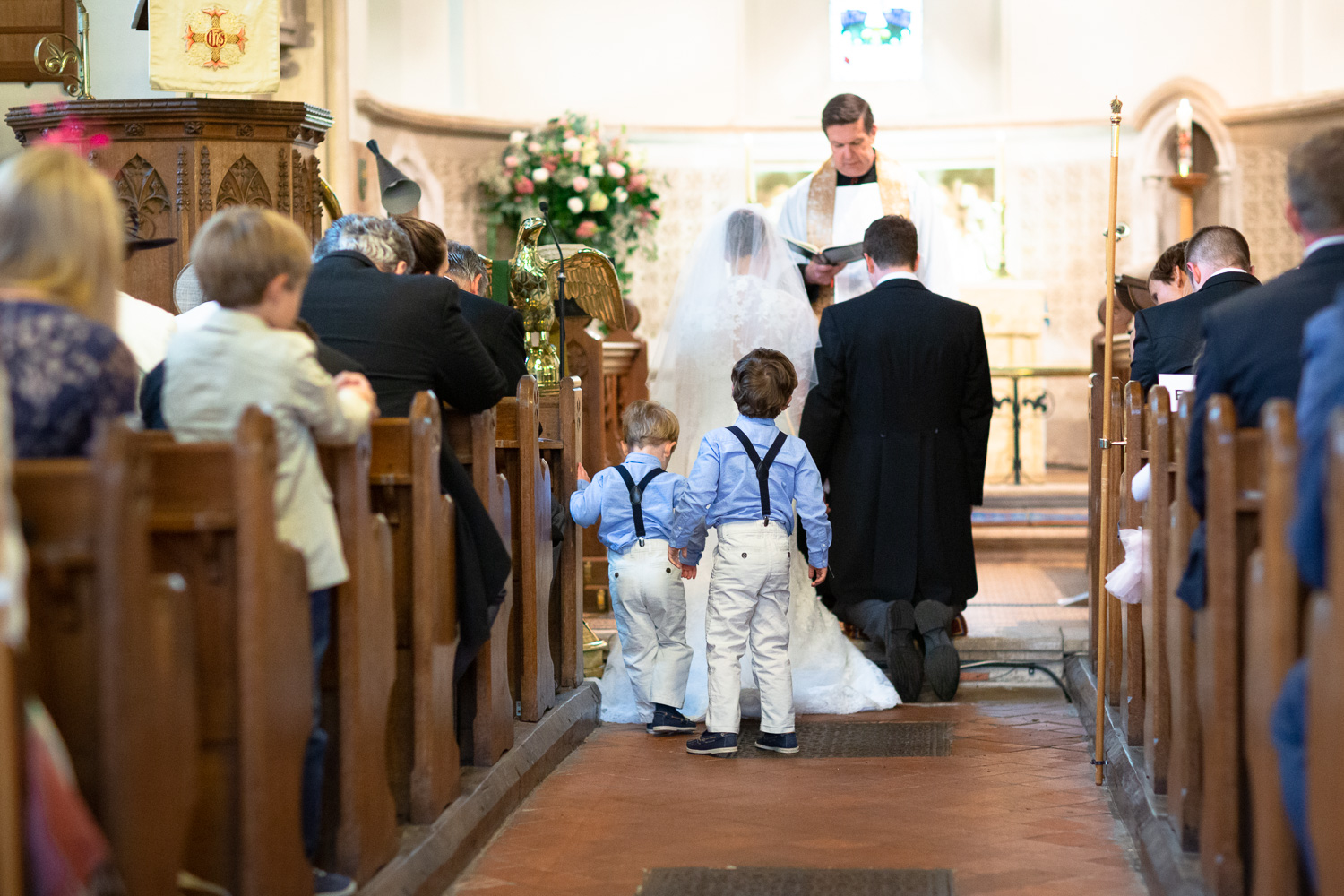 Wedding photography portfolio page boys in aisle during marriage vows