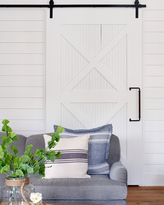Lisa Furey designed this barn door as the perfect door between her client's family room and kids' playroom. The entire family gets to relax and play in the same space, but when guests are over, they can close the door on the mess. 😊 Design is at its best when it's functional! Photo: @mcbecks_pix. Design: @lisafureyinteriors.  #interiordesign #familyfriendly #modernfarmhouse #mainlinehome #mainlinedesign #blueandwhite #myhousebeautiful