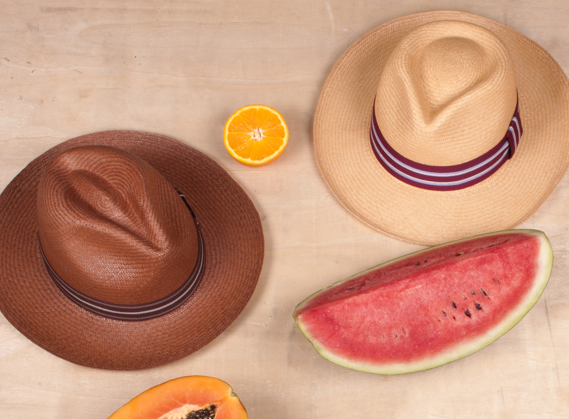 Lifestyle photograph of elegancia tropical straw panama hats with fruit