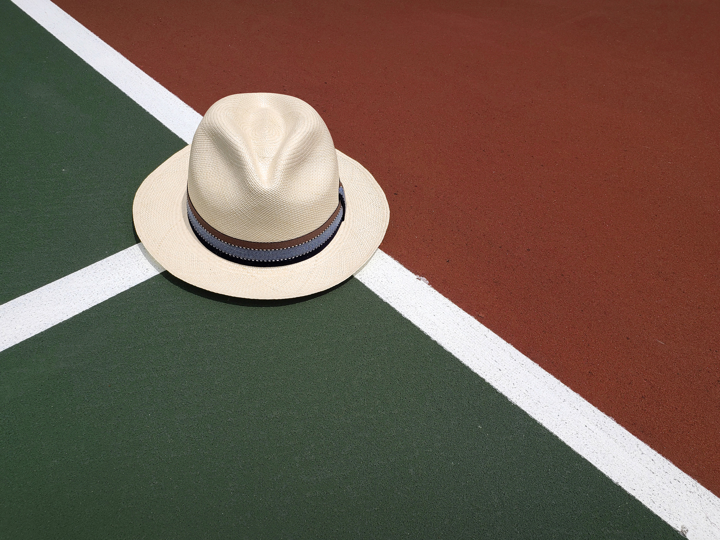 Panama hat lifestyle picture tennis court
