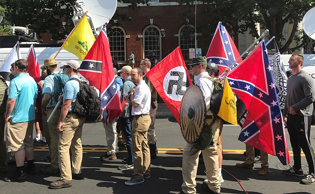 """Alt-right members preparing to enter Emancipation Park holding Nazi, Confederate, and Gadsden """"Don't Tread on Me"""" flags ( Anthony Crider )"""