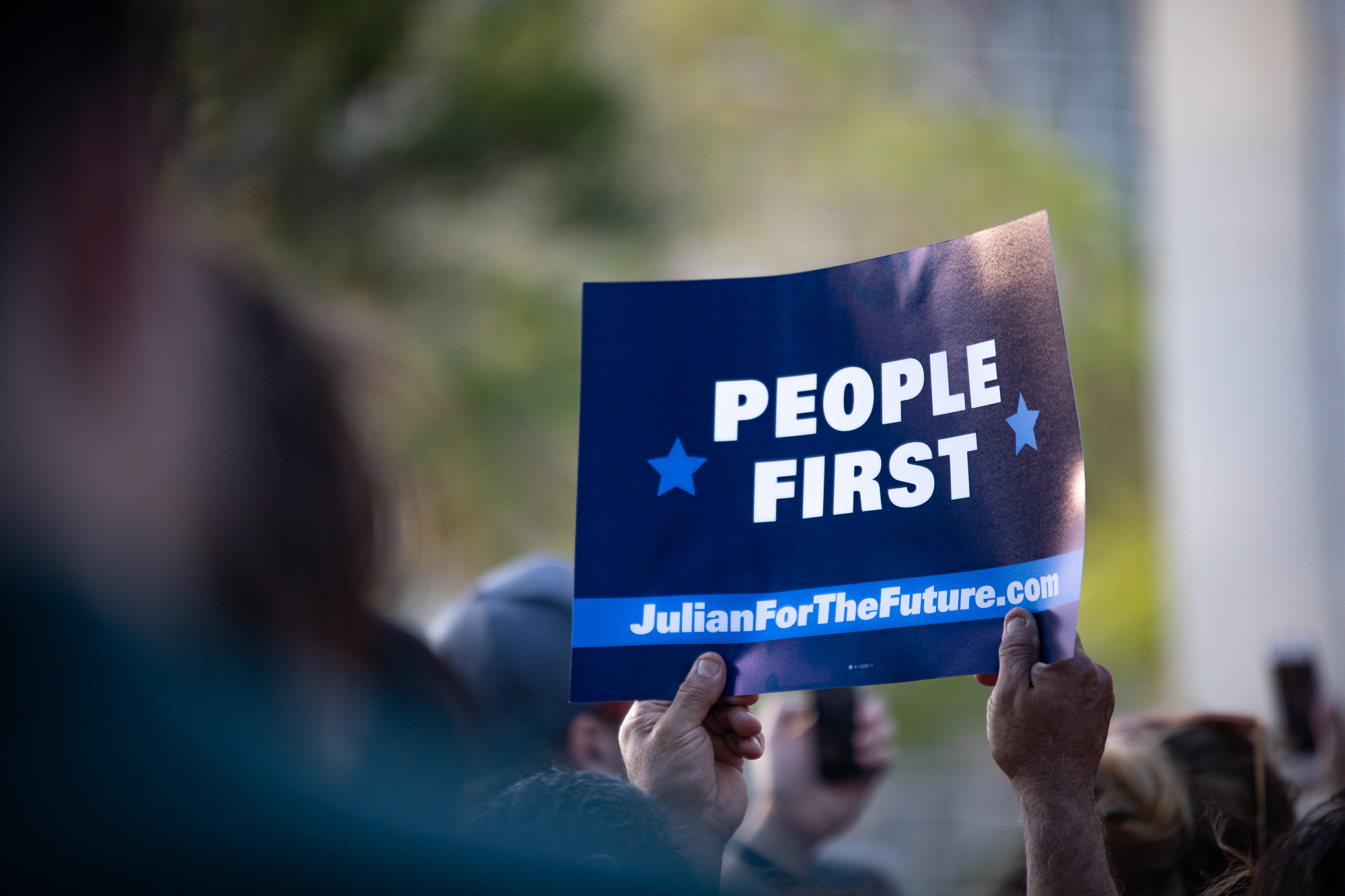 "An attendee holds up a ""People First"" sign at the Castro rally. (Photo by:  Joel Pena , Photographer - The San Antonio Sentinel)"