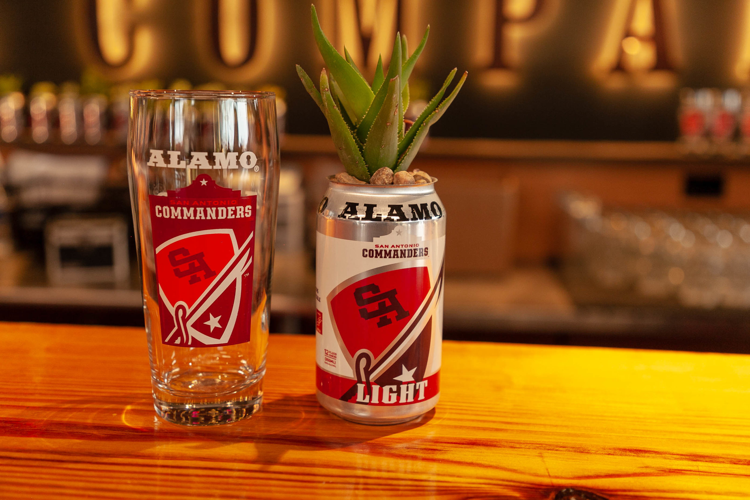 Alamo's Commanders beer cans and glasses on display at the brewery. (Photo by:  Luis Vazquez , Contributing Reporter - San Antonio Sentinel)