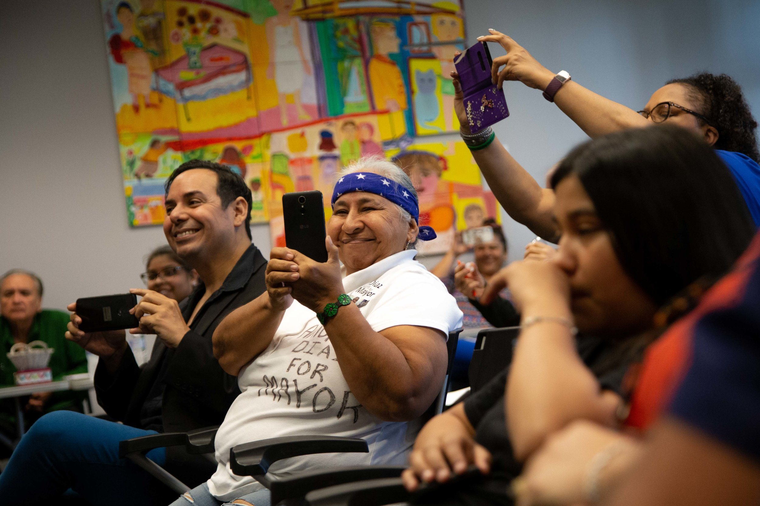 Attendees take photos of the candidates during the forum. (Photo Credit:  GA Media Productions )